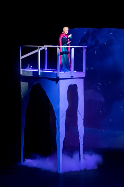 Princess Elsa, played by Hayley Sleek, singing from the tower of her Ice Castle.